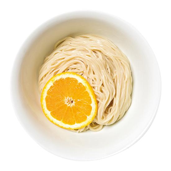 ↑夜鳴きつけそば(880円) 麺皿にはオレンジが大胆に置かれ、麺を持ち上げるとほのかに柑橘香が漂う。つけ汁の出汁は鶏と魚介がベースのすっきり系だ