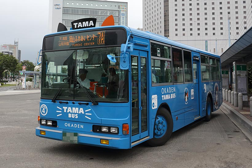 """↑岡山電気軌道はバス事業も行っている。名物""""TAMABUS""""は耳付き、車体にタマの絵が描かれる"""