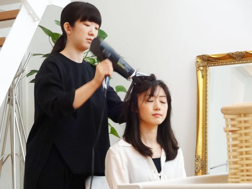 ↑ヘッドセラピスト・塩澤直子氏による実演。約50度の温風とともにマッサージ。モデルの女性も気持ちよさそう