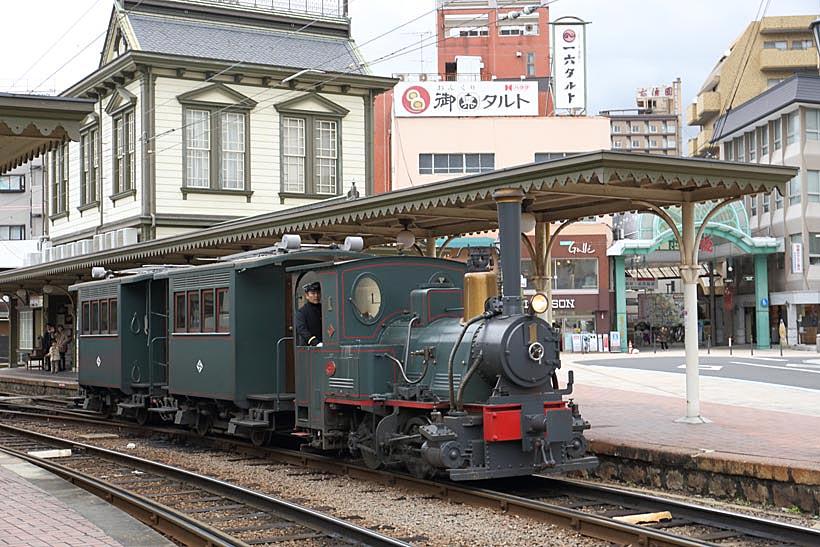 ↑道後温泉駅に停車中の坊っちゃん列車。D1形機関車が2両の客車(ハ1形)を牽引する