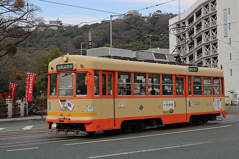 ↑松山城を仰ぎ見て走るモハ2000形。市役所前付近では松山城の堀ぞいを市内電車が走る