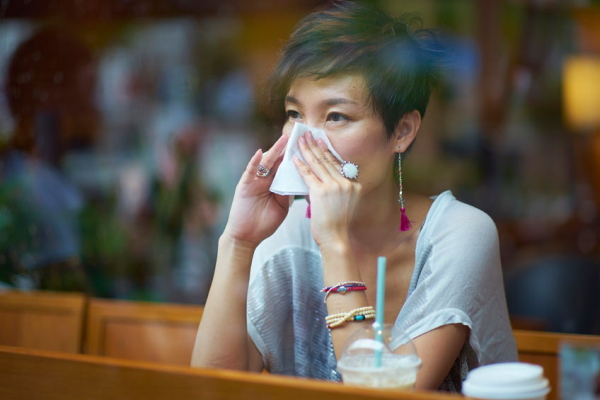 58131754 - a sick young woman blowing her nose in coffee shop