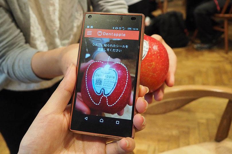 ↑デンタルチェックに使用する「Dentapple」と専用アプリを起動したスマートフォン。シールにプリントされたQRコードを撮影することでユーザーを識別します