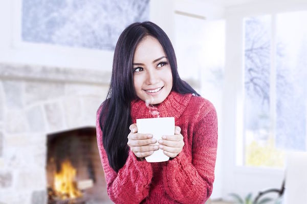 16577611 - beautiful girl is warming near fireplace while holding a cup of coffee in her hands