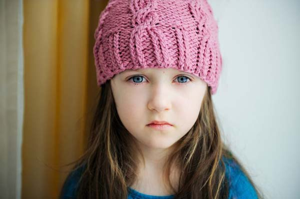 10193689 - close-up portrait of a child girl wearing pink knitted hat