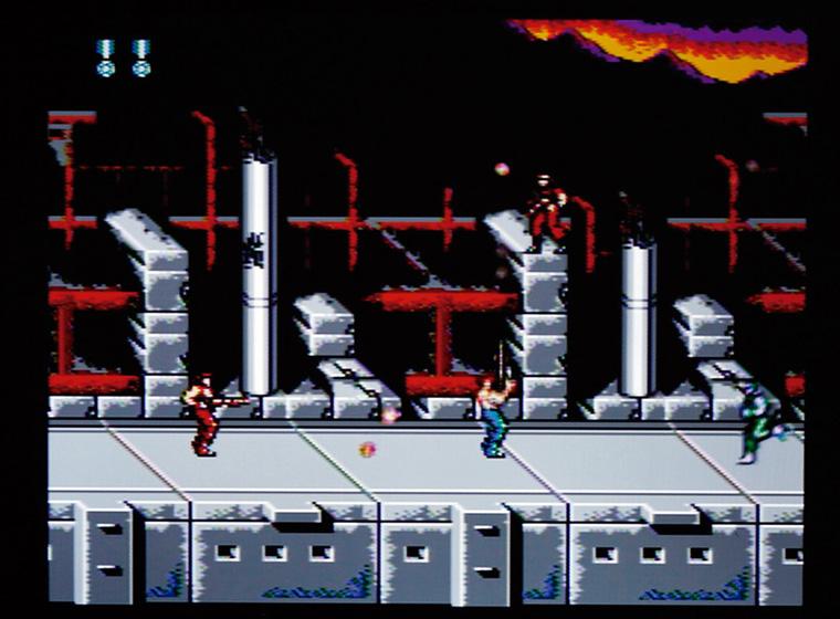 ↑横スクロールの1面で敵基地に乗り 込む1Pの「ビル」と2Pの「ランス」。 2人協力プレイが熱いのも「SUPER 魂斗羅」の人気の理由だ