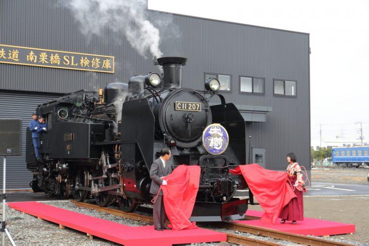↑文字は書道家・涼風花氏が揮ごう、根津嘉澄東武鉄道社長と共にヘッドマークをお披露目した