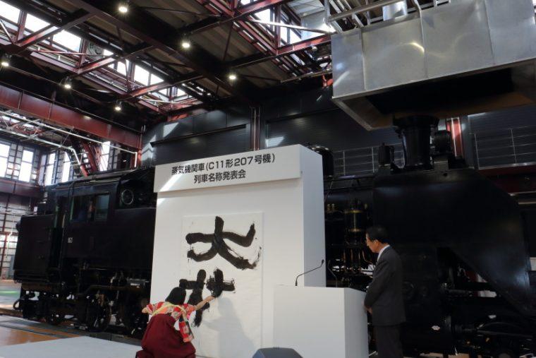 ↑南栗橋SL検修庫内で開かれた「列車名称発表会」。書道家・涼風花氏が「大樹」の字を描く