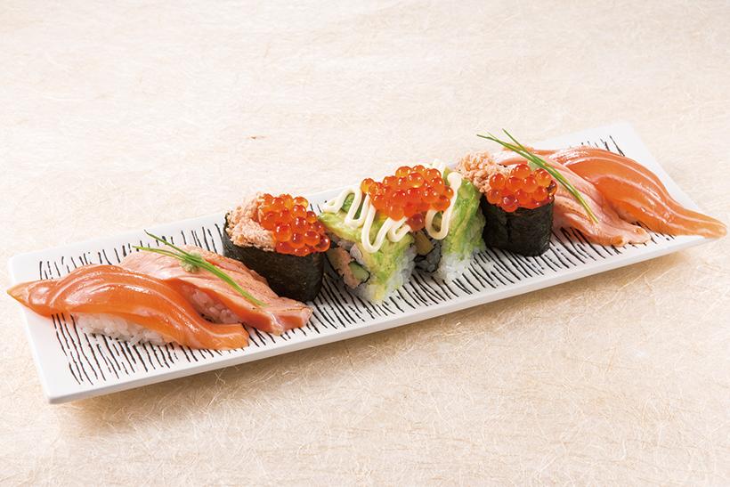 ↑サーモンまみれ(1360円) 生サーモンを使い、通常の握りや炙りと、アボカドを使った創作寿司が並ぶ。新宿駅前の系列店で先行発売され、好評だったひと皿