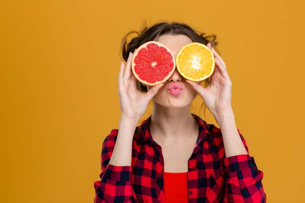 49774464 - funny playful young woman in checkered shirt holding halves of citrus fruits against her eyes and making duck face over yellow background