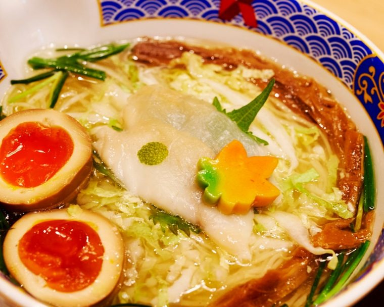 ↑ふぐだし潮らーめん美味玉入(¥1,150円)。たまり醤油で漬け込まれた玉子は、より色鮮やかに。また花の形をした麩には、四季に応じて色が変わるという粋な遊び心が込められています