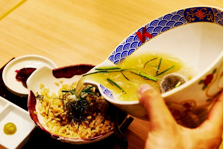 ↑ごはんの上に、あられと刻み海苔があしらわれた状態で提供。箸休めとしてしば漬けが添えられ、ワサビも別皿で用意されます。片口の器からスープを注げば、芳しいふぐ茶漬けのできあがり