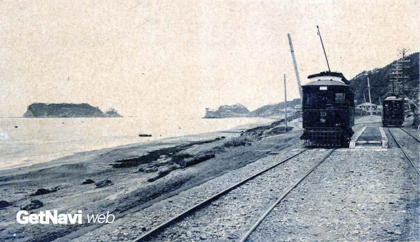 ↑大正中期の江ノ電の絵葉書。七里ヶ浜付近の波打ち際を路面電車タイプの車両が走っていた。左奥は江の島