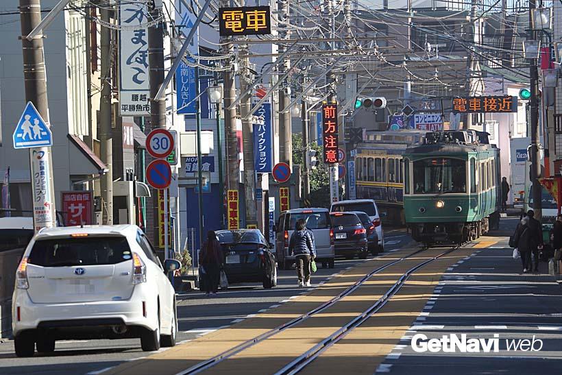 ↑通称「鎌倉市腰越電車通り」を走る20形電車。「電車接近」の表示に合わせ、車は道路脇に除けて電車の通過を待つ