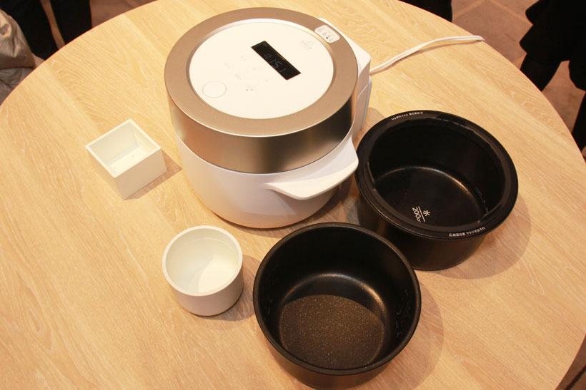 ↑枡形の米の計量カップと、円筒形をした外釜用水の計量カップを付属。2つの釜は薄いアルミ製でとても軽い。内釜・外釜ともに水量目盛付き