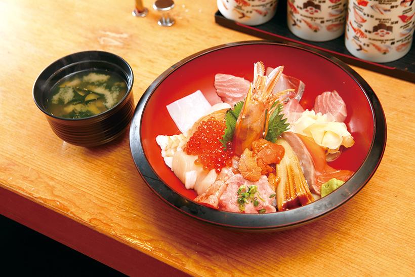 ↑海鮮丼(1598円) まぐろの中とろや有頭赤えび、うに、いくらなど12種類の魚介が、シャリを隠すほどに散りばめられる。ランチタイムはみそ汁付きで、通常1598円を1480円とおトクに提供