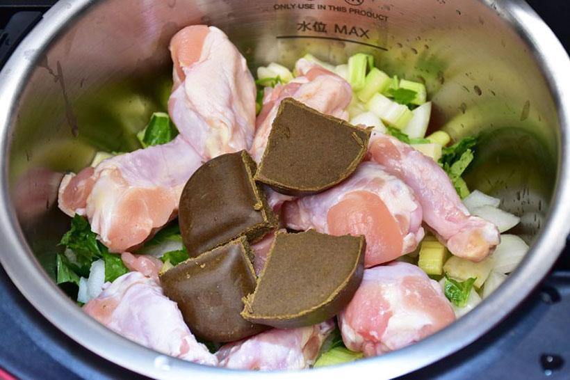 ↑トマト、タマネギ、セロリの上に鶏の手羽元、カレールウを入れたところ。トマトは見えていないが、3個しっかりと入っている