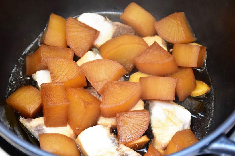 ↑最初に大根と調味液を入れ、弱火で35分じっくりと火を通して味をしみ込ませる。下ごしらえしたブリを下に敷いてから、最初に火を通した大根を載せて弱火で15分加熱