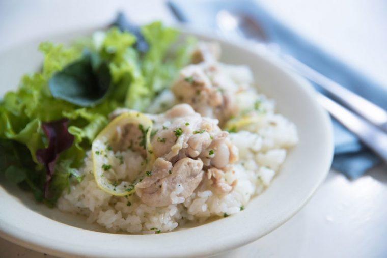 ↑鶏手羽元肉(4本)、米(2合)、輪切りレモン(5枚)、スープ(スープの素を溶かしたもの・360cc)、バター(15g)、塩(少々)、パセリ(みじん切り・大さじ1)を用意。①鶏手羽元肉は、骨に沿って浅く切り込みを入れる。米はといで水気をきる。スープを温めてバターと塩を入れて溶かす。②鍋に①を入れ、レモンをのせて炊く。③炊き上がったら、パセリを加えて全体を混ぜ、「レモンバターチキンピラフ」の完成