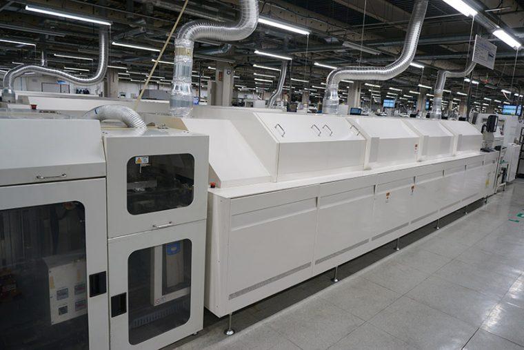 ↑こちらは基板にコンデンサなどの部品をハンダ付けするリフロー炉という機械。ハンダが焼けるニオイがします