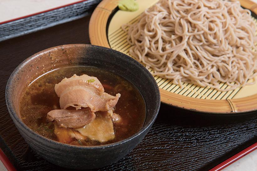 ↑ブタつけそば(580円)。そばつゆで煮込んだ豚肉が たっぷり。豚肉のうまみと コクがつゆに移り、コッテ リ好きも満足な味だ。わさ びをつけて食べても美味
