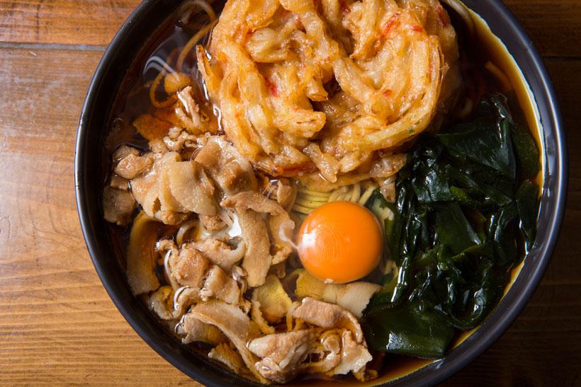 ↑松吉そば(500円)。店名を冠した「松吉そば」はミニかき揚げと豚肉、わかめ、玉子をトッピング。かき揚げは玉ねぎの甘さがすごく、豚肉はあっさり甘く煮込まれている