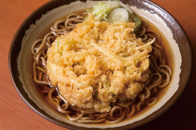 ↑天ぷらそば(350円)。玉ねぎと青ねぎを使ったシンプルなかき揚げをトッピ ング。玉ねぎの甘みと衣のコクで、つゆがさらにうまく なる