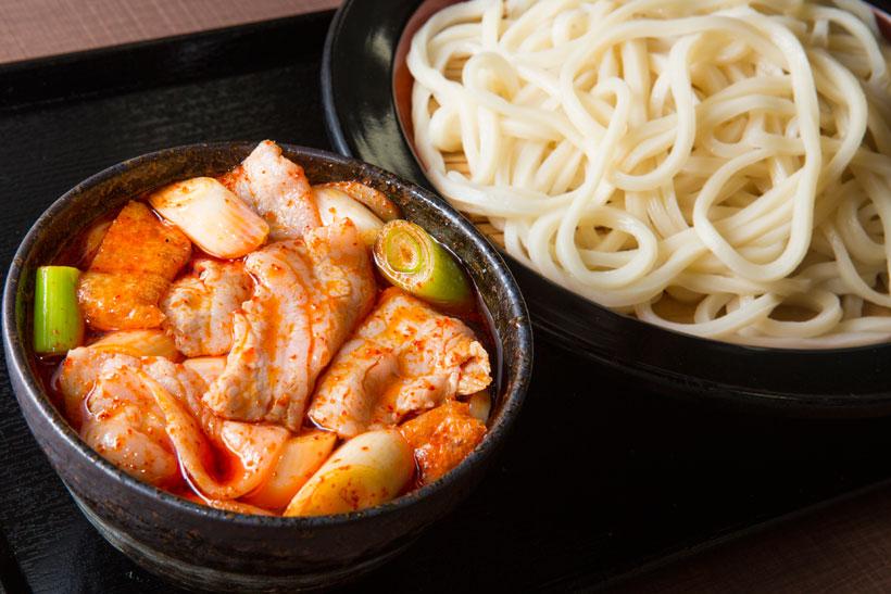 ↑旨辛肉汁うどん(並)780円。.豚肉、ネギ、油揚げが 入ったつけ汁は辛さのな かにうまみあり。うどん に合う和風の自家製ラー 油を使用