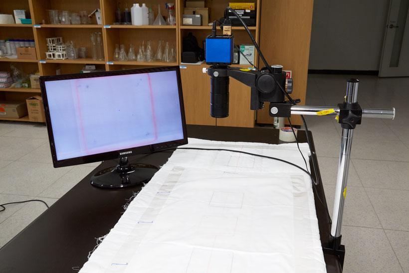 ↑ふとんを模した実験台。上部に顕微鏡が用意されており、ダニの動きがリアルタイムで分かるようになっています