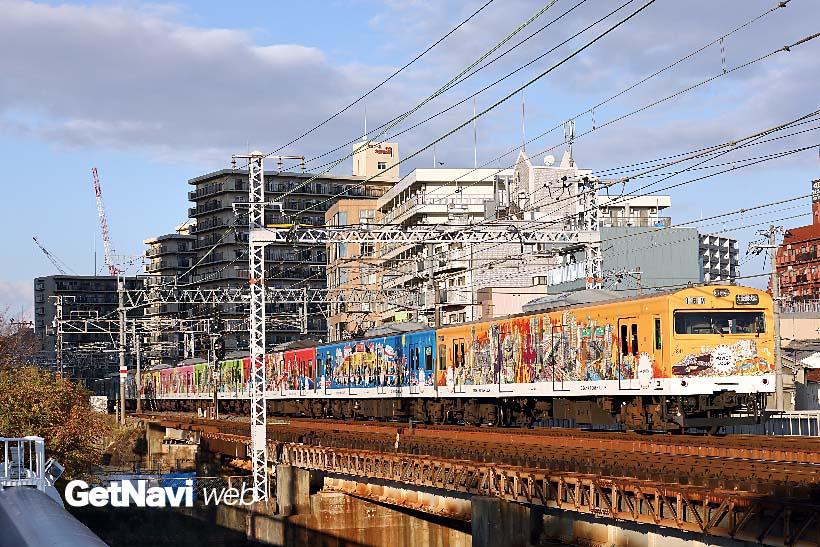 ↑派手なラッピング広告が付く103系。大阪環状線、ゆめ咲線では非常に貴重な風景となりつつある