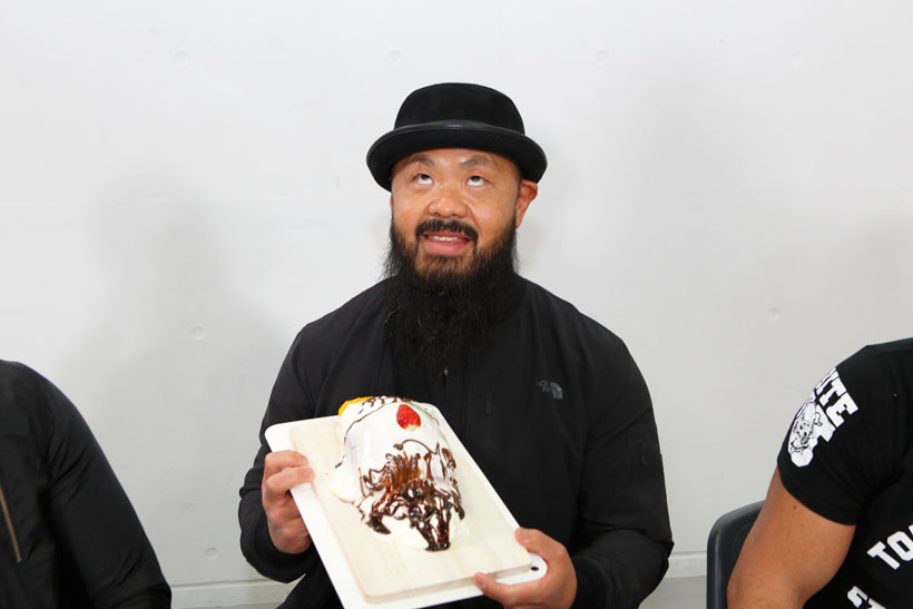 ↑「俺が食われるってことか!」と毒づきながらも、似顔絵ケーキを手におどけて見せる外道選手