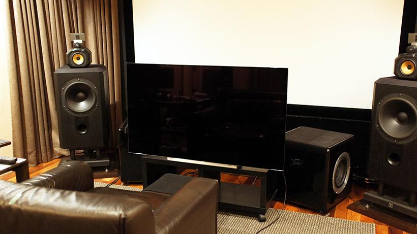 ↑自宅の視聴室に設置した状態。視聴距離は1mちょっとというかなりの近接視聴。画面が近いので後ろの120インチスクリーンと変わらないサイズ感になる