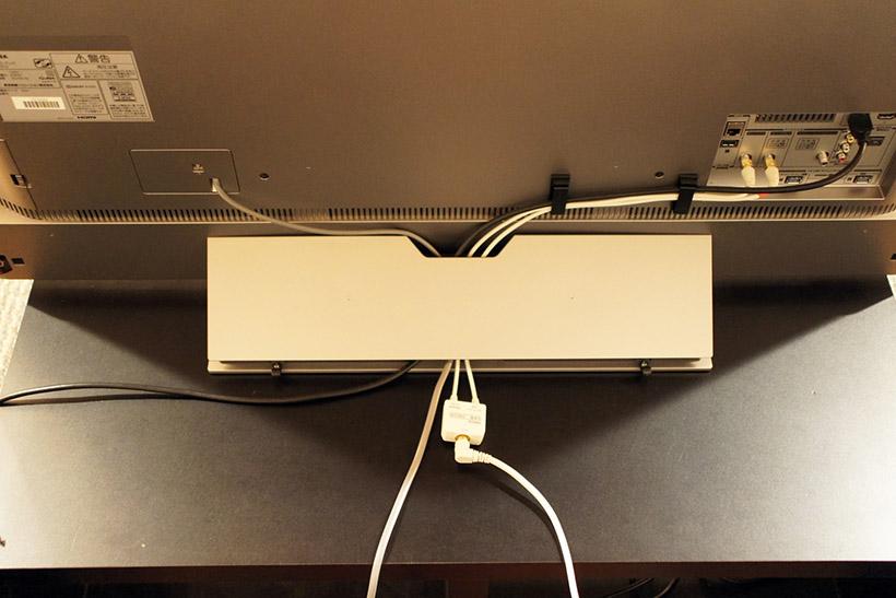 ↑55X910を後ろから撮影。ケーブル類はスタンド部分に収納できるようになっており、配線などもすっきりと整理できる。後日、転倒防止のためのバンドなどの取り付けを行っている