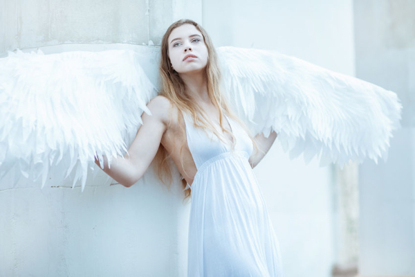 65782859 - beautiful girl with white wings standing near a white wall