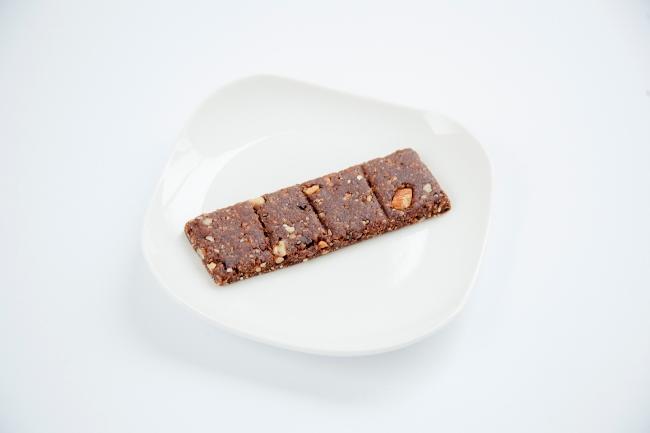 スナックミーのオリジナルのフルーツバー第1弾「snaq.bar cocoa」。有機ドライフルーツやナッツ、チアシードなどがふんだんに入っている