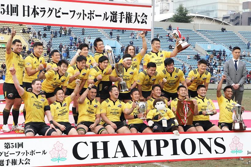↑日本選手権で優勝し、歓喜するサントリーのフィフティーンと沢木敬介監督(右端)。監督就任1年目で2冠を達成した