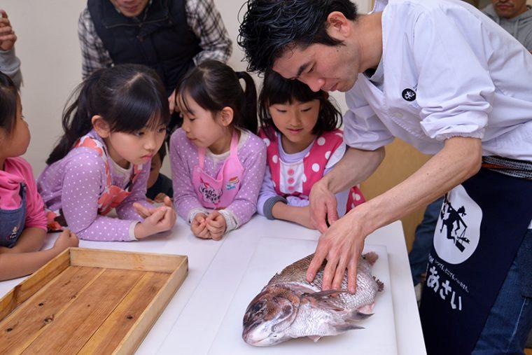 ↑鯛のおかしら付きの造りを完成させたのは浅井さん。子どもたちは興味津々