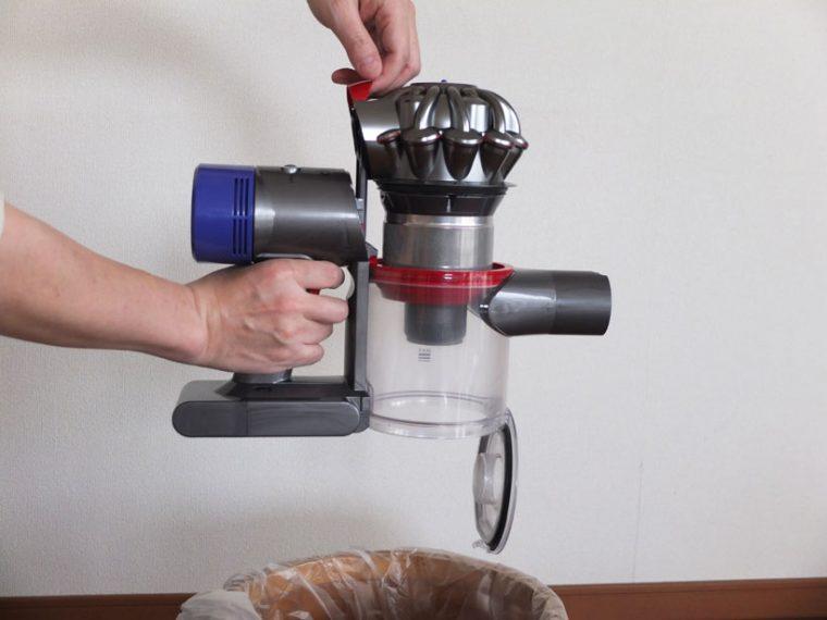 """↑ダストビン後ろの赤いレバーを上に引き上げると、ダストビンとメッシュ状の""""シュラウド""""が上に持ち上がります。そこからさらにレバーを引くとダストカップ底部のふたが開いてゴミが下に落ちる仕組みです。最初にレバーを引いてシュラウドが持ち上がる際に、ダストカップの上部に設置された赤いラバー製の""""スクレイパー""""でシュラウドに付着したゴミをこそぎ落とし、シュラウドの掃除の手間を減らしてくれます"""