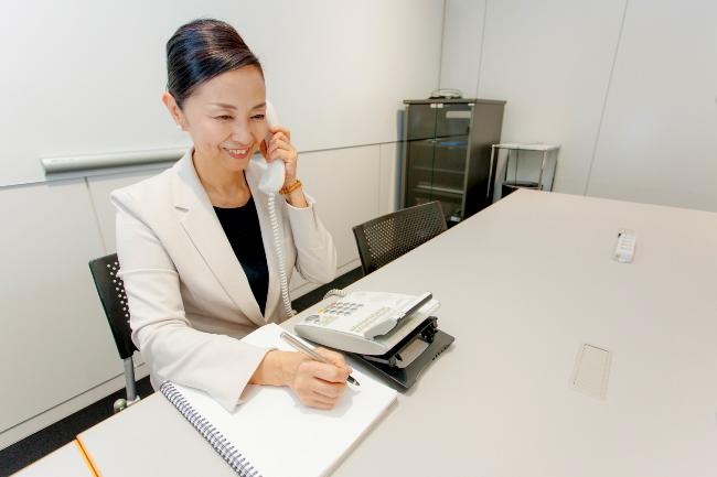 電話応対は背筋を伸ばし、まっすぐ座り、顎を引くと声が安定する。笑顔で明るい声を演出。利き手でメモを取り、反対の手で受話器を持つ。受話器は口から2、3センチほど離す