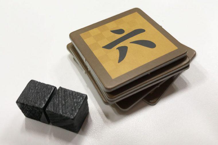 ↑「一」から「七」までの数字が書かれた『注力チップ』(「四」は2枚あり)。左の黒い立方体が『機密