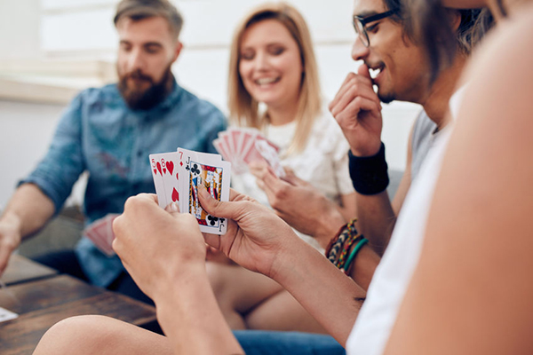 52407747 - group of friends sitting together playing cards. focus on playing cards in hands of a woman during a party.