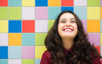47210960 - happy girl laughing against a colorful tiles background. concept of joy