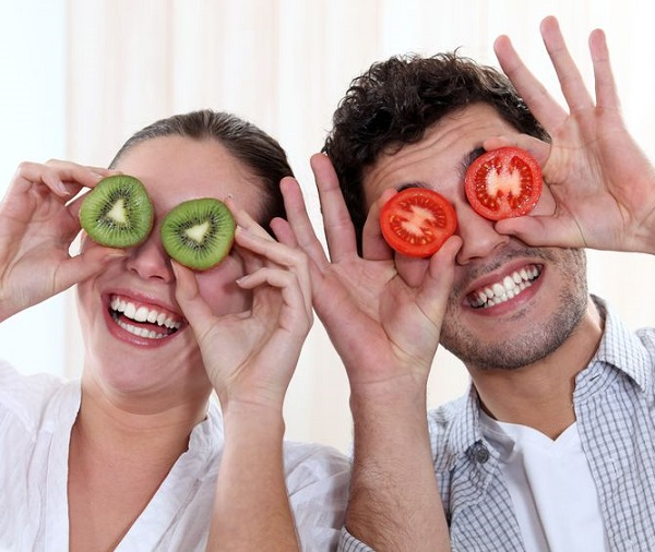 15449146 - funny couple covering their eyes with fruit