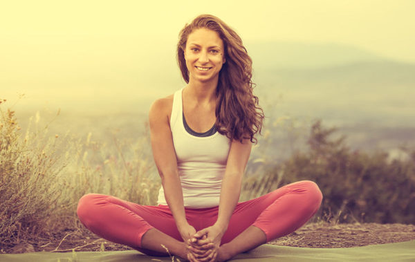 50413973 - young woman sits in yoga pose with city on background. freedom concept. calmness and relax, woman happiness. toned image