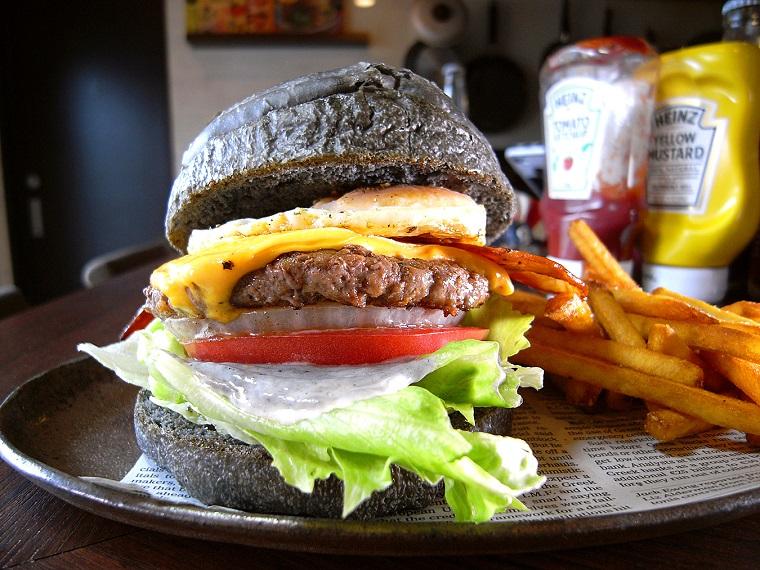 ↑「デラックスバーガー」(1200円)。自家製黒バンズとブラックペッパーソースの組み合わせにチーズ&エッグ、スモークベーコンのフレーバーがクンと品よく香る