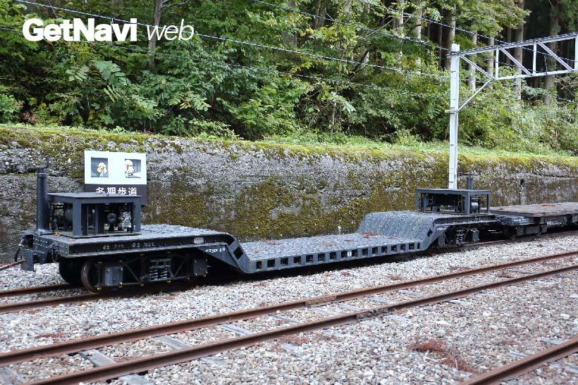 ↑出平駅に置かれた大型機器を運ぶ貨車・大型車。後ろには冬期歩道が設けられている