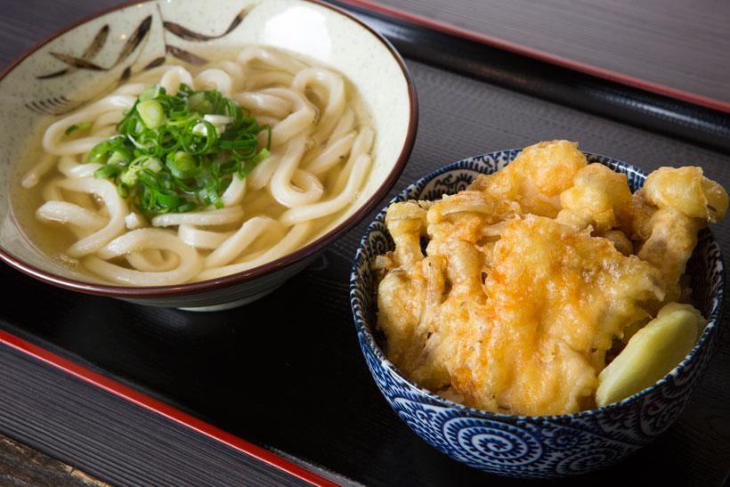 ↑きのこ天丼うどんセット(550 円)。.その日に仕入れた旬のきのこを2種類選んで天ぷらに。揚げたて天ぷらに染み込むタレのうまみが食欲を刺激する。かけうどんも付いて大満足