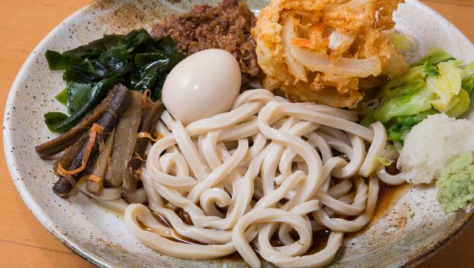↑五葵スペシャルA(冷)(530円+500円)。キャベツや馬肉の甘辛煮、か き揚げ、煮卵など具沢山な一 皿。最初はその硬さに驚くが、 次第にワイルドな味の虜に