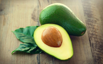 52913817 - avocado. organic avocados with leaves on a wooden table