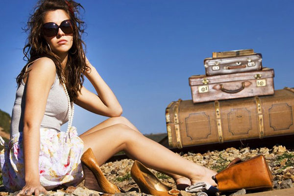9670128 - young traveling woman with her suitcases along the road